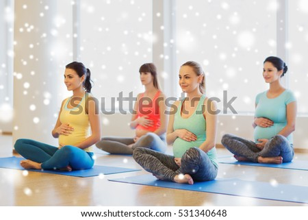 pregnancy, sport, fitness, people and healthy lifestyle concept - group of happy pregnant women exercising yoga in lotus pose in gym over snow