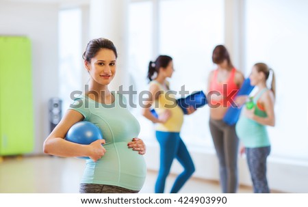 pregnancy, sport, fitness, people and healthy lifestyle concept - happy pregnant woman with ball in gym - stock photo