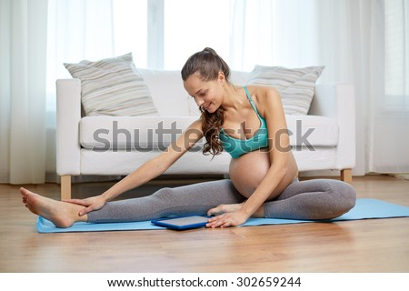 pregnancy, sport, people and technology concept - happy pregnant woman with tablet pc computer exercising and stretching leg on mat at home - stock photo