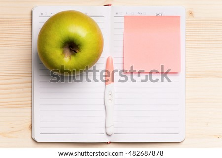 Pregnancy test on blank opened book for new message. Blank paper and green apple on a wooden table- view from above.