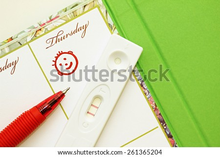 Pregnancy test with a positive result and female weekly. - stock photo