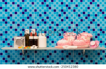 Pregnancy test with medicaments and pills on bath shelf on blue background - stock photo