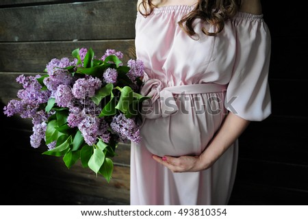 Pregnancy. Woman holding a bouquet of lilacs.
