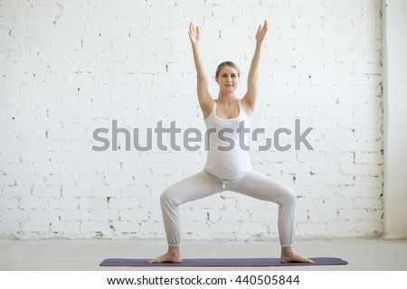 Pregnancy Yoga and Fitness concept. Portrait of beautiful young pregnant yoga model working out indoor. Pregnant happy fitness person enjoy yoga practice at home. Prenatal Goddess or Sumo Squat Pose - stock photo