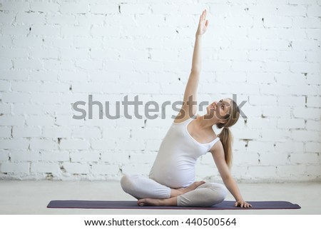 Pregnancy Yoga and Fitness concept. Portrait of young pregnant yoga model working out indoors. Pregnant fitness person practicing yoga at home. Prenatal side stretching in position with crossed legs - stock photo