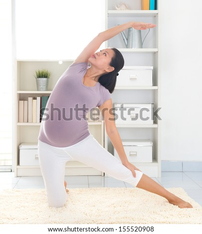 Pregnancy yoga meditation. Full length healthy 8 months pregnant calm Asian woman meditating or doing yoga exercise at home. Relaxation yoga kneeling side stretch positions. - stock photo