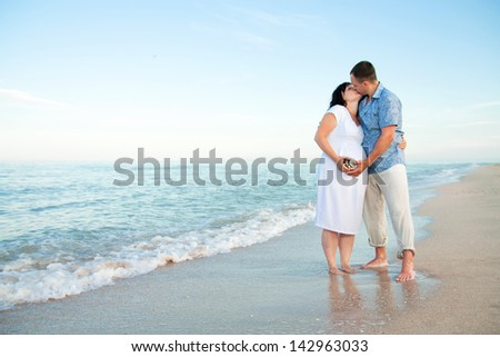 Pregnancy. Young loving couple on the beach. Happy family.