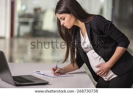 Pregnant adult businesswoman working  at her working place in office. - stock photo
