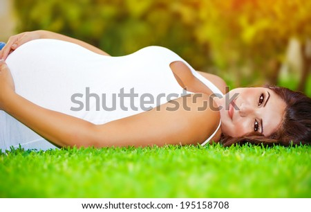 Pregnant arabic woman lying down on fresh green grass field, touching her belly, summer holidays, happy pregnancy concept - stock photo