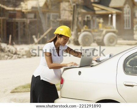 Pregnant Asian businesswoman with laptop at construction site - stock photo