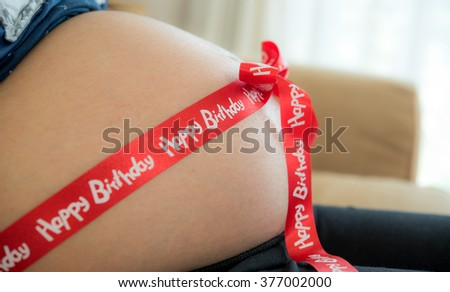pregnant belly decorated with ribbon as a present - stock photo
