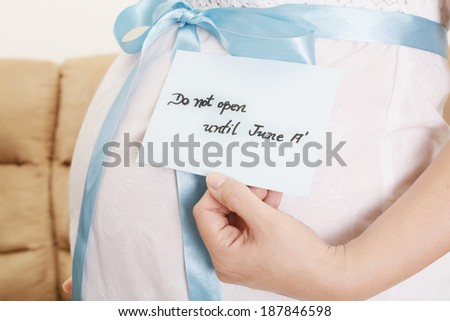 Pregnant belly with a light blue ribbon and a tag saying do not open until - stock photo
