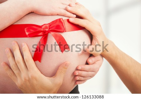 pregnant belly with red ribbon and hands of parents mom and dad - stock photo