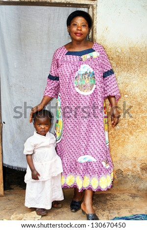 Pregnant black African mother and baby girl in front of their house