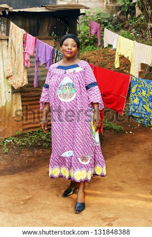 Pregnant black African woman in her backyard with clothesline. - stock photo
