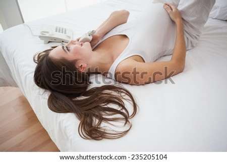 Pregnant brunette on the phone in bed at home in the bedroom - stock photo