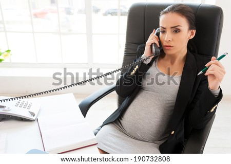 Pregnant business lady. Beautiful pregnant businesswoman talking on the phone while sitting at her working place in office  - stock photo