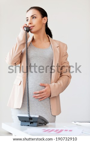 Pregnant business lady on the phone. Beautiful pregnant businesswoman talking on the phone and smiling while standing near her working place in office  - stock photo