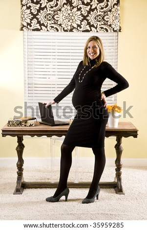 Pregnant businesswoman posing by her home desk - stock photo