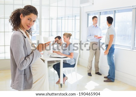 Pregnant businesswoman sending text with team behind her in the office - stock photo