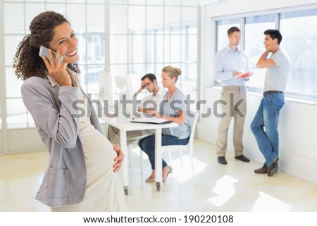 Pregnant businesswoman talking on phone with team behind her in the office - stock photo
