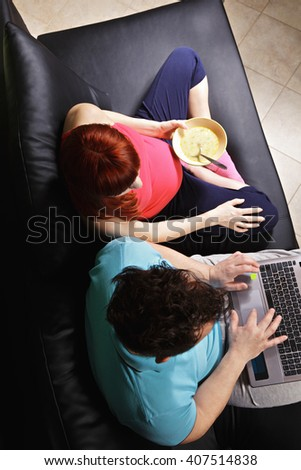 Pregnant caucasian couple sitting on sofa she holds bowl of soup while he works on laptop above view - stock photo