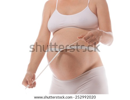pregnant caucasian woman closeup body solated on white background studio shot measuring measurement