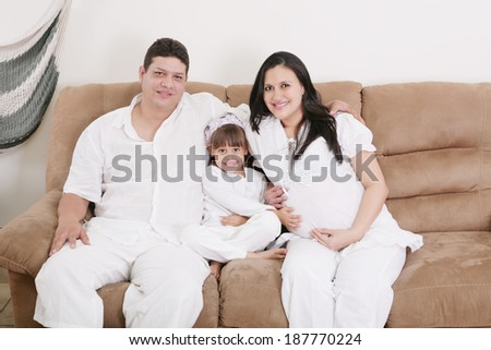 pregnant couple enjoying with their daughter - stock photo