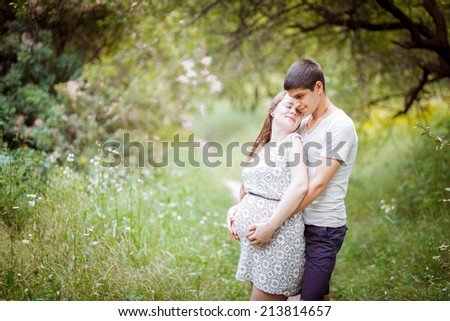 Pregnant couple holding his stomach