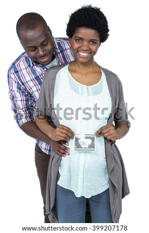 Pregnant couple holding ultrasound scan on white background
