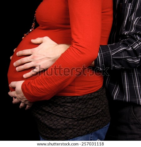 pregnant couple in closeup holding belly over black background - stock photo