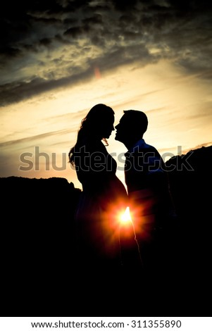 Pregnant couple silhouettes at sunset