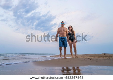 Pregnant couple walking on the beach