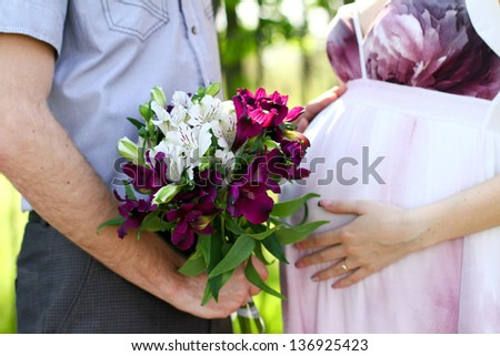 Pregnant couple with bouquet of flowers in  summer park