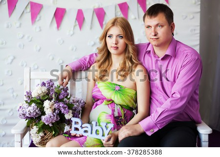 pregnant couple with lilac flowers - stock photo