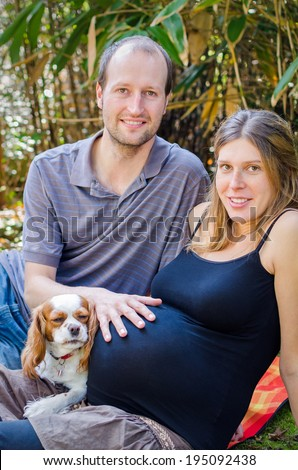 Pregnant couple with their dog outdoors at the park. - stock photo
