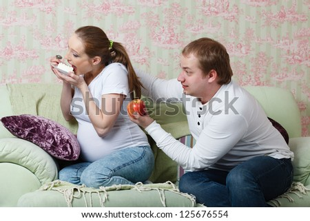Pregnant family sit on a sofa at home with  an apple and cake. Concept of healthy food. - stock photo
