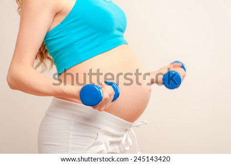 Pregnant female do exercise, side view, body part, lifting dumbbells, active and sportive pregnancy, healthy motherhood concept - stock photo