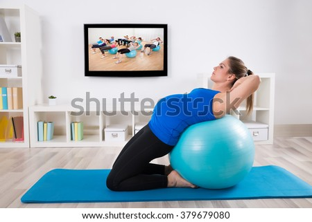Pregnant Female Doing Workout On Fitness Ball In Front Of Television - stock photo