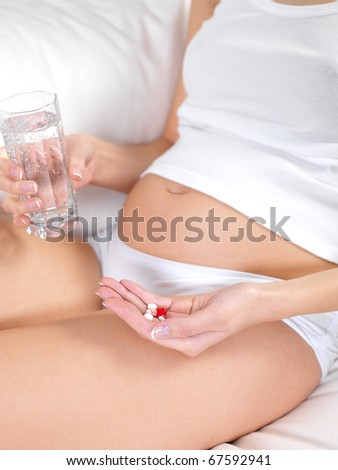 Pregnant female with glass of water and tablets in hands - indoors