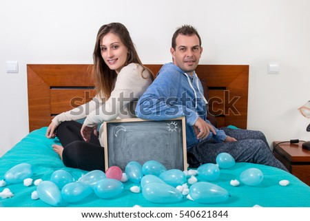 pregnant girl and husband in the bed with a black chalkboard.