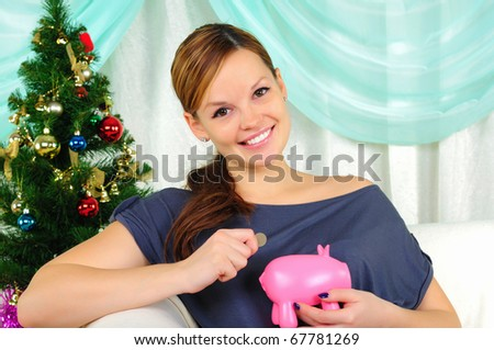 Pregnant girl make a wish and holding a piggy bank. Happy New Year! - stock photo
