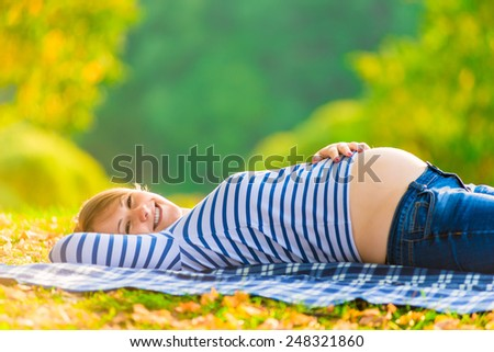 pregnant girl. Portrait of a pregnant woman relaxing in the park - stock photo