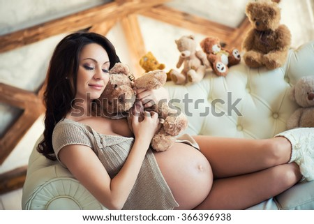 Pregnant girl with brown teddy bear sitting on the couch. Love and Motherhood - stock photo