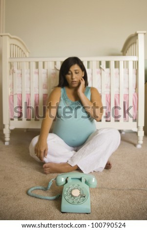 Pregnant Hispanic woman looking at telephone next to crib