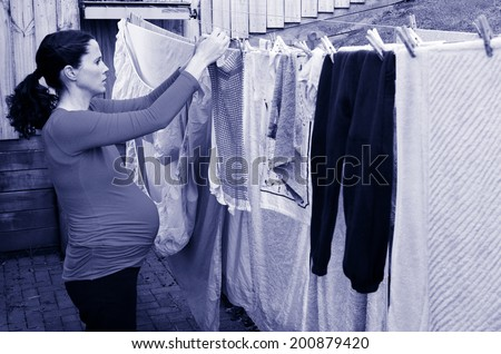 Pregnant housewife woman doing housework pegging out washing to dry on clothes line during pregnancy.Concept photo of pregnancy, pregnant woman lifestyle and health care.copyspace - stock photo
