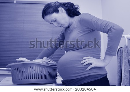 Pregnant housewife woman doing housework, washing family clothes, during pregnancy.Concept photo of pregnancy, pregnant woman lifestyle and health care. crop image - copyspace (BW) - stock photo