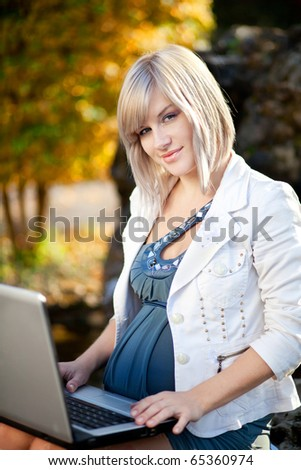 Pregnant lady using her laptop outdoor