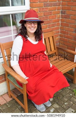 Pregnant lady with glasses wearing a red dress and hat with a big smile sitting in front of her house on a wooden bench