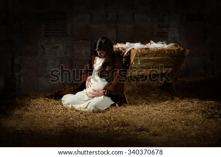 Pregnant Mary leaning on the manger on Christmas Eve - stock photo